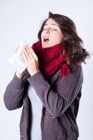 estornudo: Muchacha bonita joven con el frío del invierno
