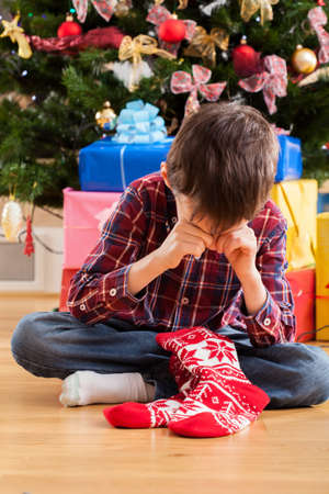 Christmas stocking - boy dissatisfied with christmas present Stock Photo