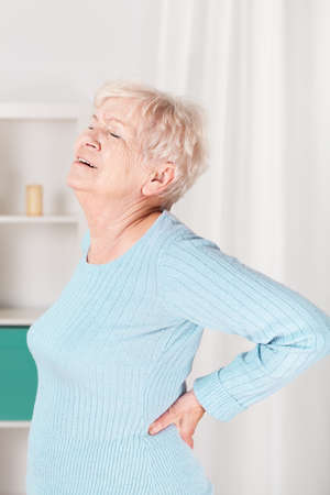 spinal disks: Vertical view of grandpa suffering from back pain Stock Photo
