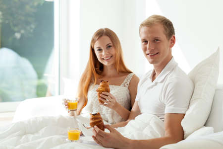 rest room: Couple eating breakfast in bed at hotel room