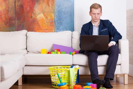 babysitting: Elegant man using laptop surrounded by toys