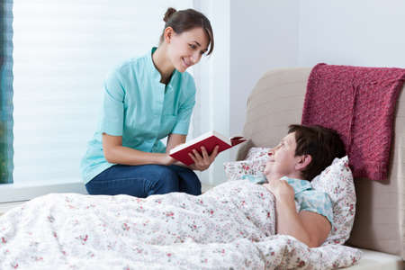 home health care: Helpful nurse reading book patient lying in bed
