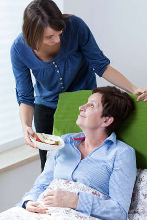 home health care: Vertical view of girl giving grandma apple Stock Photo