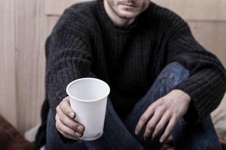 limosna: Hombre sin hogar joven que se sienta en el suelo y pide ayuda Foto de archivo