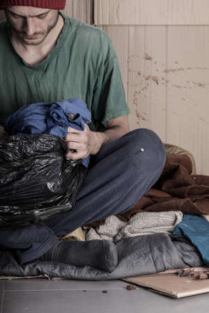 Homeless young man looks a bag of clothes photo