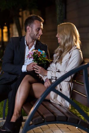 bunch up: An elegant man giving his date a bunch of flowers on a bench