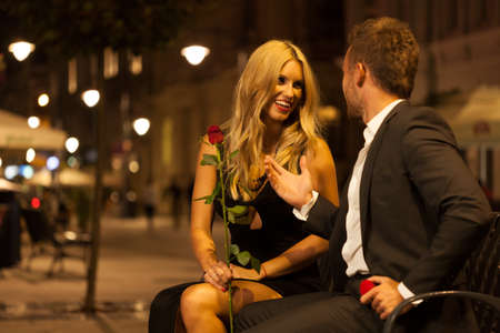 A beautiful elegant couple having a funny conversation on a bench photo
