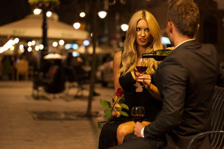 proposing a toast: A couple having an elegant toast with red wine at night Stock Photo