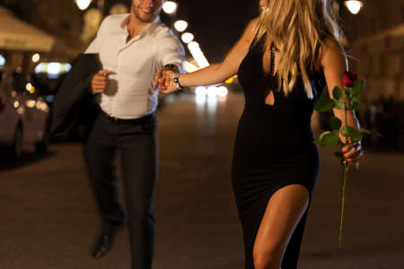 An elegant couple holding hands when running on a date at night photo