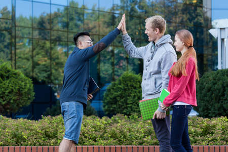 Asian boy giving friend a high five photo