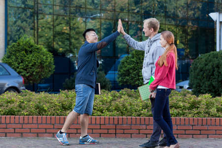 Asian young man giving friend a high five photo