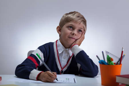 fineliner: Boy wearing sweater doing homework at the desk Stock Photo