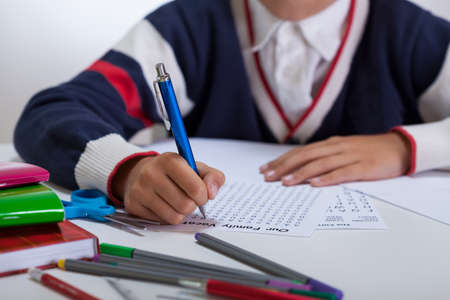 schoolkid search: Close-up of schoolboy doing wordsearch at the desk
