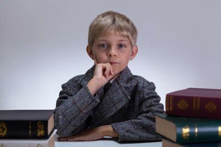 Little child in tweed jacket around encyclopedias