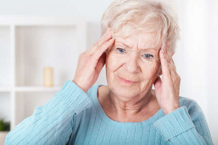 cephalgia: Senior woman having headache and touching her temples