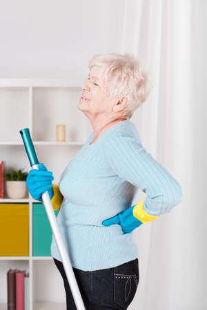 personas de espalda: Mujer mayor que tiene dolor durante el piso de contralavado