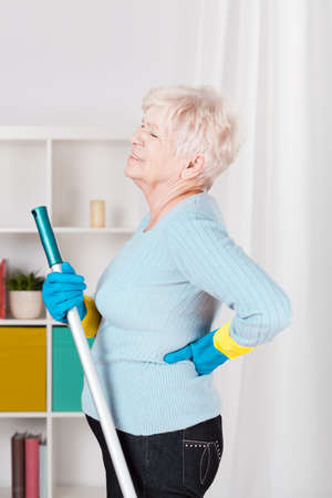 pain: Senior woman having back pain during washing floor Stock Photo
