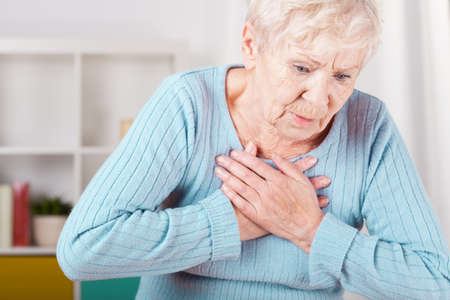 senior pain: Portrait of elderly woman having heart attack