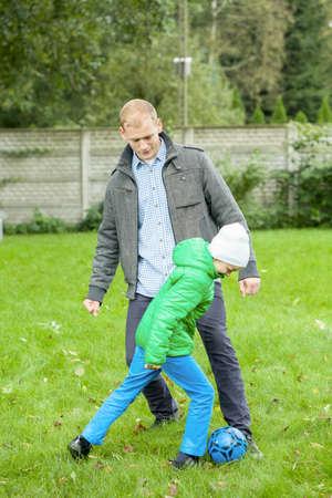 niños jugando en el parque: Padre que juega al fútbol junto con el hijo en un jardín
