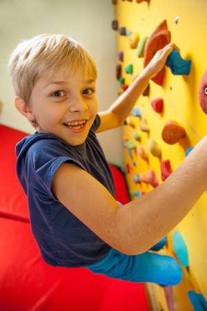 niño trepando: Muchacho feliz en el muro de escalada, vertical