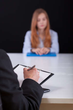 write: Close-up of employer writing down during the recrutiment meeting Stock Photo