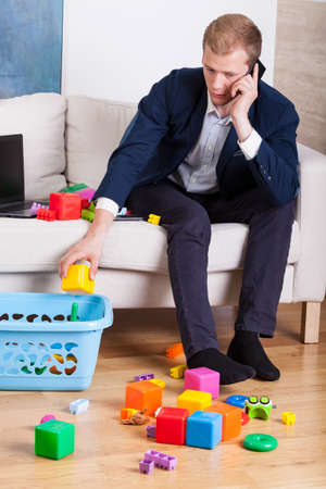 Elegant man cleaning up toys while talking on the phone photo