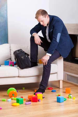 babysitting: Glum man sitting on sofa in dirty living room