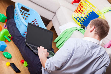 dirty room: Man using laptop sitting on the floor in dirty drawing room