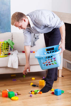 house clean: Stay-at-home dad cleaning up drawing room Stock Photo