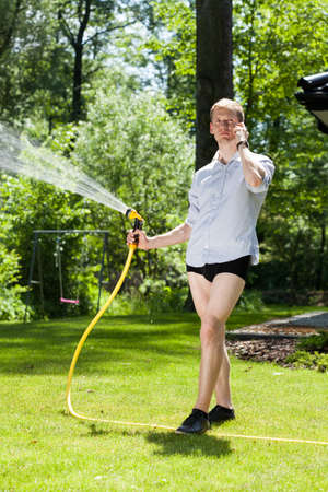 Man without trousers watering the plants in garden photo