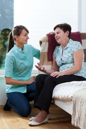 Nurse talking with female patient at her home