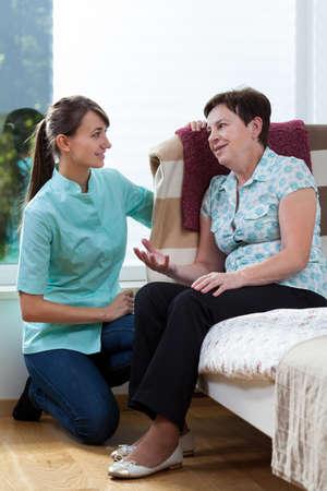 Verpleegkundige praten met de vrouwelijke patiënt bij haar thuis