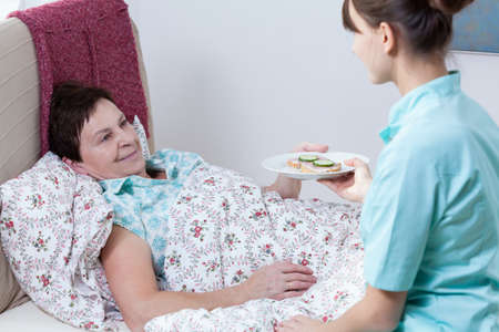 Horizontal view of nurse giving patient meal photo