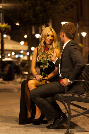 A good-looking couple talking on a bench in the city at night photo