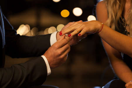 rose ring: A closeup of a man putting an engagement ring on his girlfriends hand