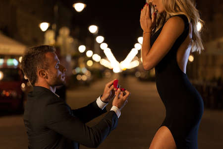 A man in a suit proposing to his beautiful woman at night photo