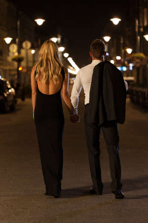 A chic woman and elegant man in a city at night