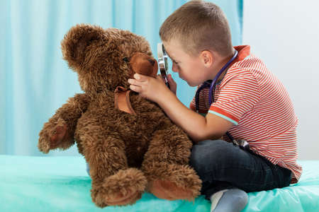 Little boy playing on doctor and examining teddy bear photo