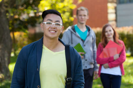 Asian boy and his university friends holding folders photo