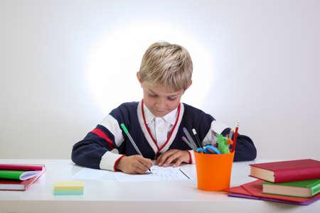 fineliner: Little schoolboy doing homework at the desk