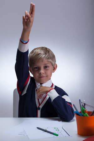 Top of the class raising his hand at school Stock Photo