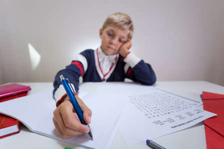 Horizontal view of bored boy writing in notebook