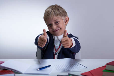 fineliner: Horizontal view of cute schoolkid showing thumbs up Stock Photo
