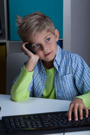 Image of schoolboy talking on the phone photo