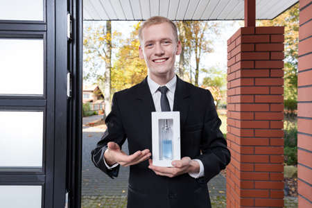 Smiling salesman standing at the door and selling perfume