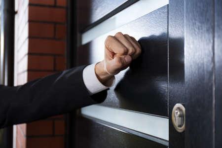 tocar la puerta: Primer plano de la mano tocando la puerta