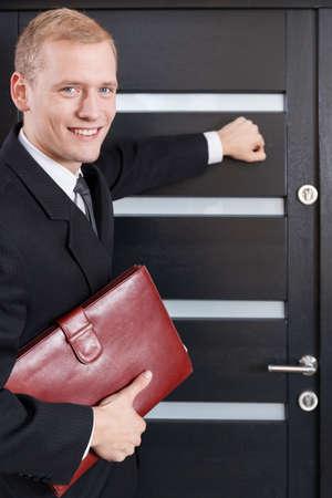 tocar la puerta: Retrato de vendedor de puerta en puerta llamando a la puerta Foto de archivo