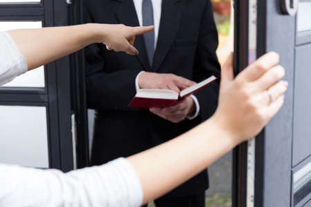 house of prayer: Woman ordering Jehovahs witness to go out Stock Photo