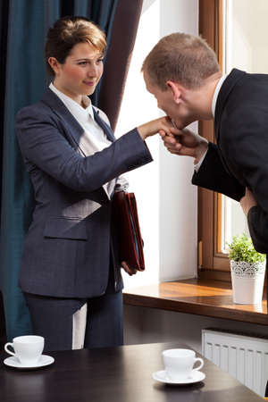 Eleganter Geschäfts küssen Frau in der Hand