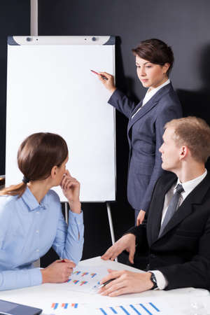Manager writing on the board during business meeting photo